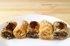 Row of delectable Baklava sweets on a white plate served on wooden table. Food Background stock photography