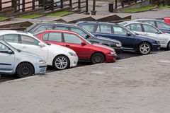Row of diagonally parked cars in the city street Stock Image