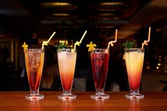 Row of different cocktails with straws on a dark background royalty free stock image
