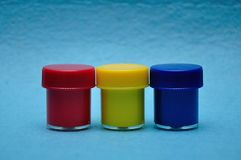 A row of different colors paint. On a blue background royalty free stock images