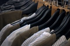 Row of different coloured shirt on hanger, clothes on hangers in a store or showroom stock image