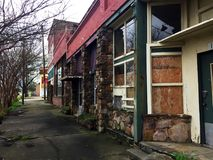 Row of dilapidated buildings on a forgotten sidewalk stock images