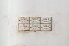 Row of Dirty Light Switches on Stained Concrete Wall Royalty Free Stock Image