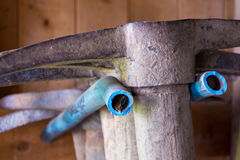 Row of dirty old stacked pickaxes in shed with gardening tools Royalty Free Stock Image