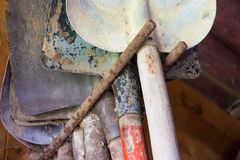 Row of dirty old stacked shovels on rail in outhouse with vintag Royalty Free Stock Photography