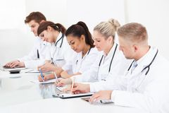Row of doctors writing at desk Royalty Free Stock Image