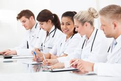 Row Of Doctors Writing At Desk Stock Photo