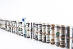 Euro Height. Row of dollar rolls with a euro banknote in the middle isolated on white Royalty Free Stock Photography