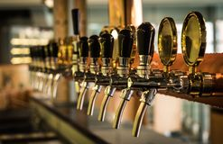 Beer tab on the bar. Row of draft beer tab on the top of counter bar in closeup view, time of celebration, selective focus Stock Image