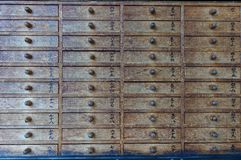 Draw a Fortune. A Row of Draws Containing Fortunes at a Japanese Srhine. The kanji numbers are from top right to bottom left 41 - 90 stock image