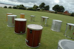 Row of Drums. A row of various size and shape drums laid out on grass. Photographed at an angle Royalty Free Stock Photography