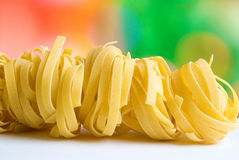 Row dry nest pasta on colored background Stock Images