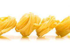 Row dry nest pasta on white. With reflection Stock Photography