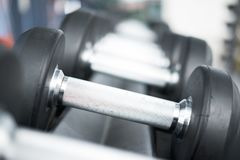 Row of dumbbells in gym. Black dumbbell set in sport fitness cen. Row of dumbbells in gym. Black dumbbell set in sport fitness club center Stock Photo