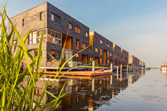 Row of Dutch modern canal houses in Almere. Reflected in the water stock photography