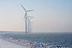 Row of Dutch windmills disappearing in winter haze. Long row of Dutch windmills disappearing in winter haze royalty free stock photography