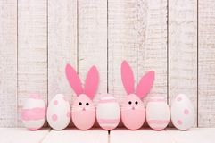 Easter eggs against white wood, two with bunny faces and ears. Row of Easter eggs against a white wood background. Two with bunny faces and ears Royalty Free Stock Photo