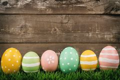 Row of Easter eggs on grass over rustic wood Royalty Free Stock Image