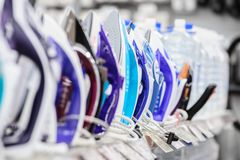 Row of electric irons in retail store stock images