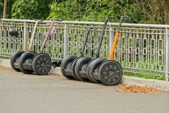 A row of electric scooters on the asphalt road near the gray fence. In the park stock photos