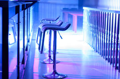 Row of Empty Bar Stools Along Bar in Night Club Royalty Free Stock Photography