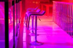 Row of Empty Bar Stools Along Bar in Night Club Royalty Free Stock Photos