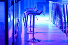 Row of Empty Bar Stools Along Bar in Night Club Stock Photo