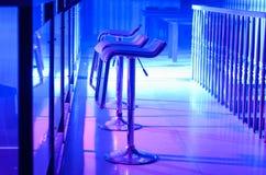 Row of Empty Bar Stools Along Bar in Night Club Stock Photo
