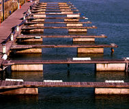A row of 13 empty boat jetties on water. A row of 13 empty boat jetties in a repeating line on blue water in a marina, creating an abstract pattern Royalty Free Stock Photography