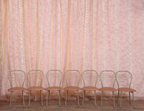A row of empty chairs against a theater curtain. in the theater. Stock Photography