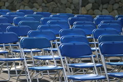 Row of empty chairs outdoors. Rows of empty blue chairs or seats outdoors Stock Photography