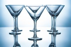 Row of empty martini glasses on grey. With reflections stock photography