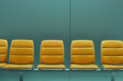 Row of empty orange chairs against gray wall Stock Photos