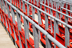 Row of empty red seats in a sports stadium. With metal railings viewed diagonally close up in a full frame view Stock Image
