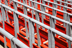 Row of empty red seats in a sports stadium. With metal railings viewed diagonally close up in a full frame view Stock Photography