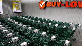 Row of empty shopping carts in front of buy low foods supermarket stock video