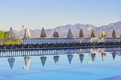 Row of empty sunbeds by the pool and the sea in the morning at dawn. Comfortable high-rise hotel stock images