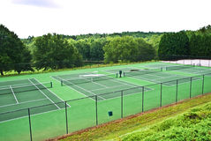 A Row of Empty Tennis Courts. Tennis courts that have been abandoned because of wet weather, there are puddles of water on some Stock Images