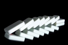 A row of fallen dominoes. On black stock photos