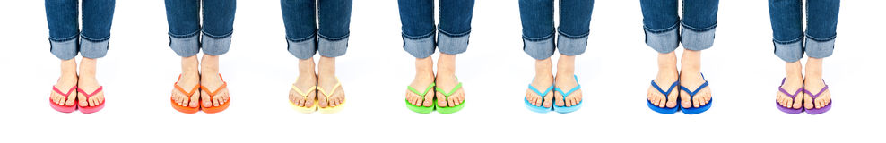 Row of Feet Wearing Colorful Flip Flops Royalty Free Stock Photography