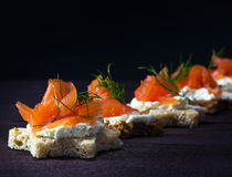 Row of festive canapes in star shape with smoked salmon on dark Stock Photo