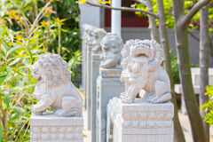 Row of fierce stone lion figures one facing the camera. Laoshan,China 21/04/2016 Row of fierce stone lion figures outside handrail decoration in a temple in royalty free stock images