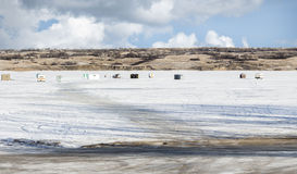 Row of fishing huts lined up along the snowy frozen lake in winter. Stock Images