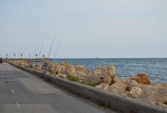 A Row Of Fishing Rods - Rocky Road Near Sea Royalty Free Stock Photo