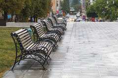 Row of five benches on the street in the rain Royalty Free Stock Photo