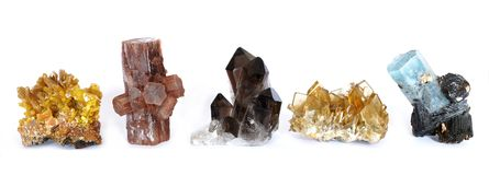 Mimetite, Aragonite, Smoky Quartz, Baryte and Aquamarine with Tourmaline crystals. A row of five crystal clusters; Mimetite, Aragonite, Smoky Quartz, Barite Royalty Free Stock Image