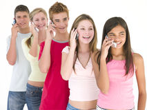 Row of five friends on cellular phones smiling Royalty Free Stock Images