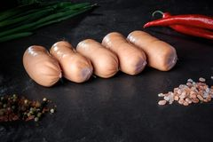row of five raw short thick sausages with chili and onion royalty free stock photos