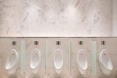 Row of five urinals with infrared sensor, on marble wall, in men's public toilet Stock Photos