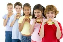 Row of five young friends eating hamburgers. Looking at camera Stock Photo